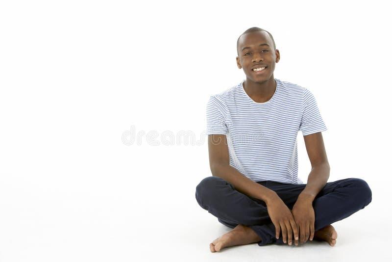 tonårs- sittande studio för pojke royaltyfri foto
