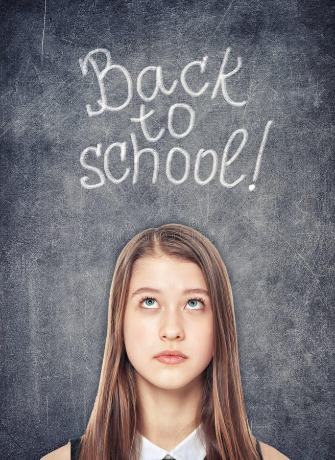 Tonårs- skolaflicka som ser upp på svart tavlabakgrunden arkivbild