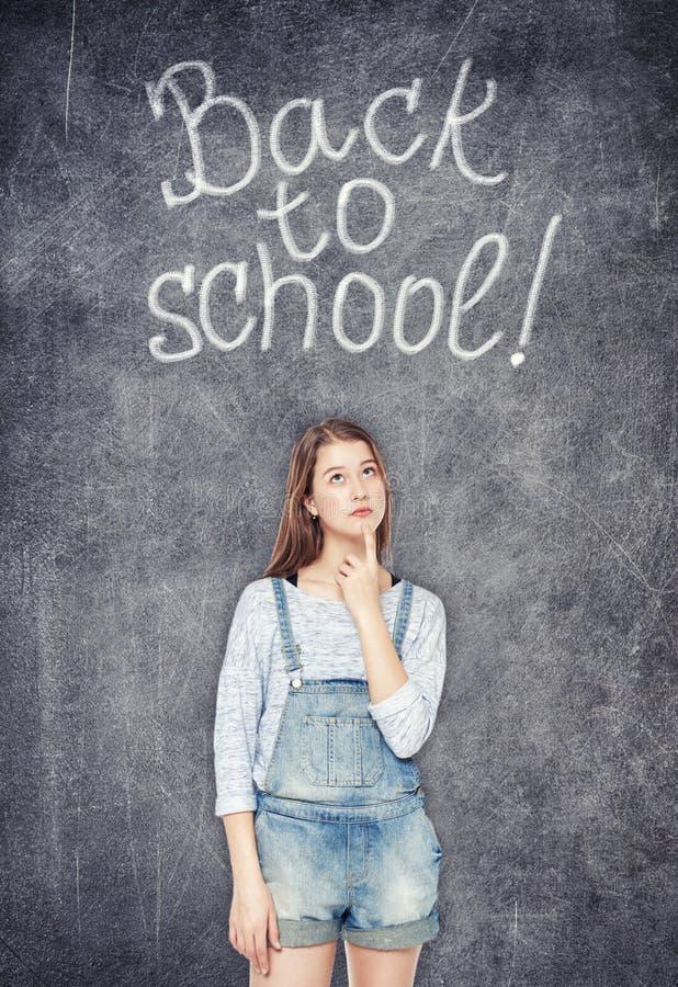 Tonårs- skolaflicka som ser upp på svart tavlabakgrunden royaltyfria foton