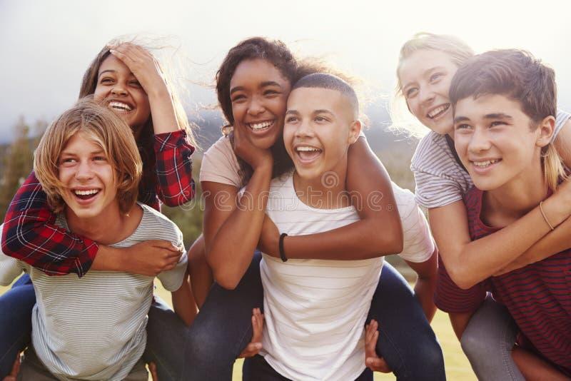Tonårs- skolavänner som har gyckel som utomhus piggybacking royaltyfri foto