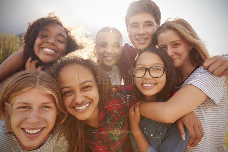 Tonårs- skolavänner som ler till kameran, slut upp arkivfoto