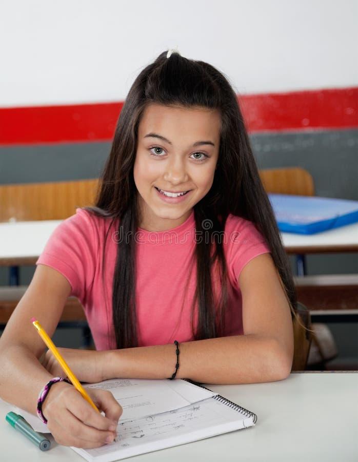 Tonårs- skolflickahandstil i bok royaltyfri bild