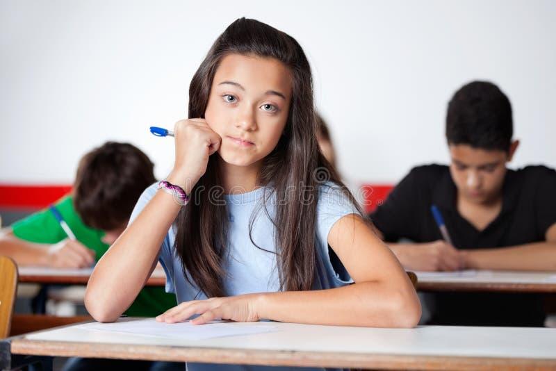Tonårs- skolflickasammanträde på skrivbordet royaltyfri bild