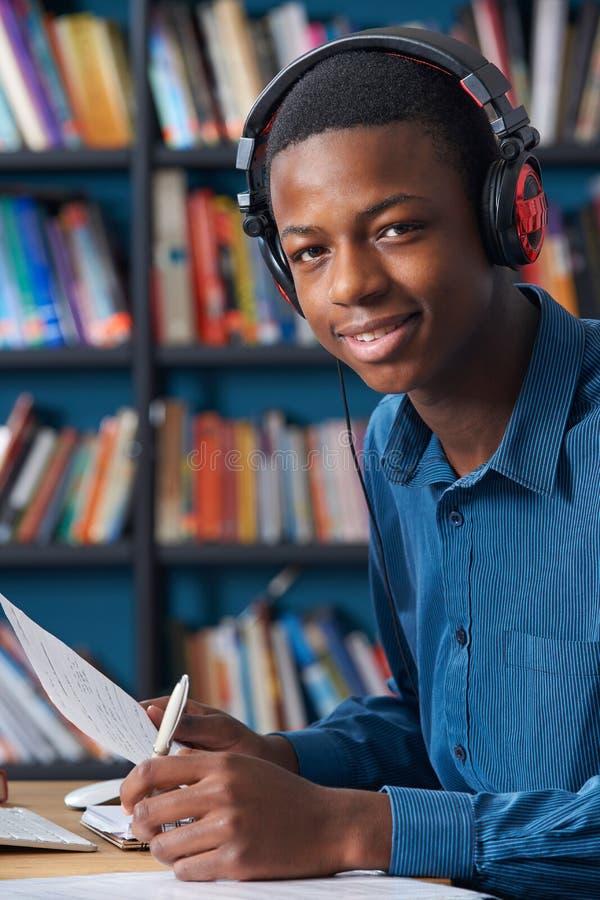 Tonårs- student Wearing Headphones Whilst som arbetar i arkiv royaltyfri bild