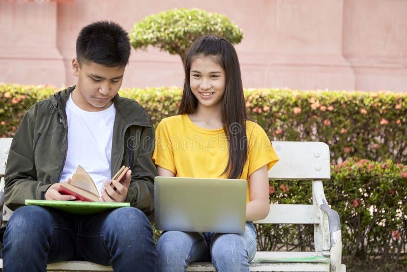 Tonårs- studenter arbetar skolajobb på bärbara datorn arkivfoton