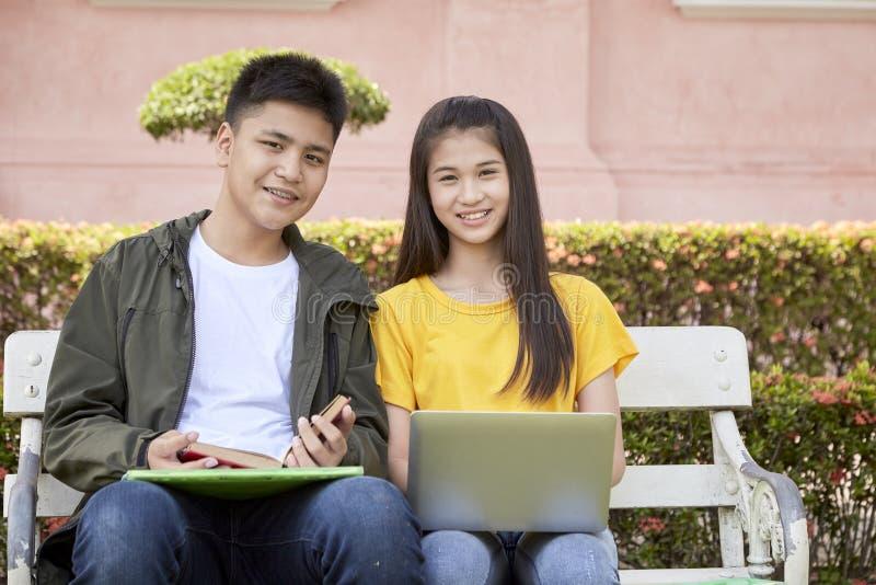 Tonårs- studenter arbetar skolajobb på bärbara datorn arkivbilder