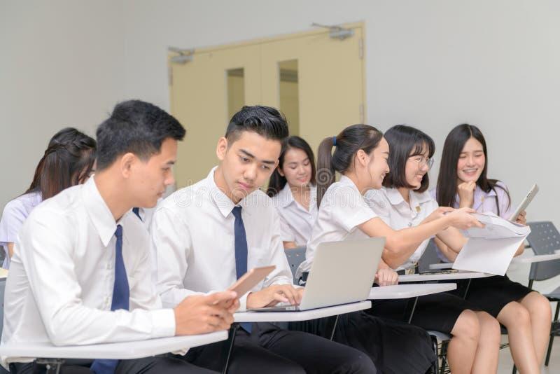 Tonårs- studenter i likformigarbete med bärbara datorn i klassrum arkivbild