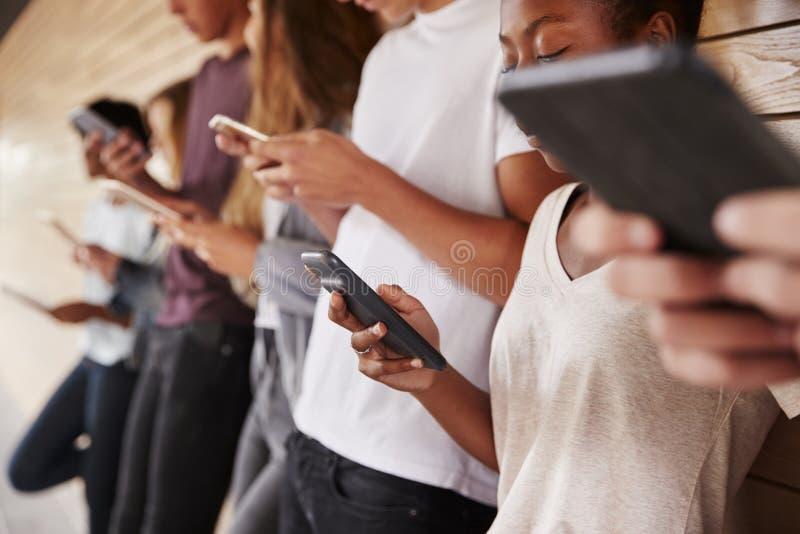 Tonårs- studenter som använder Digital apparater på högskolauniversitetsområde arkivfoton