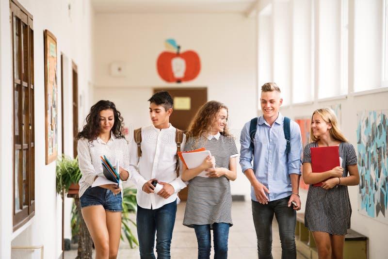 Tonårs- studenter som går i högstadiumkorridoren som talar arkivfoto