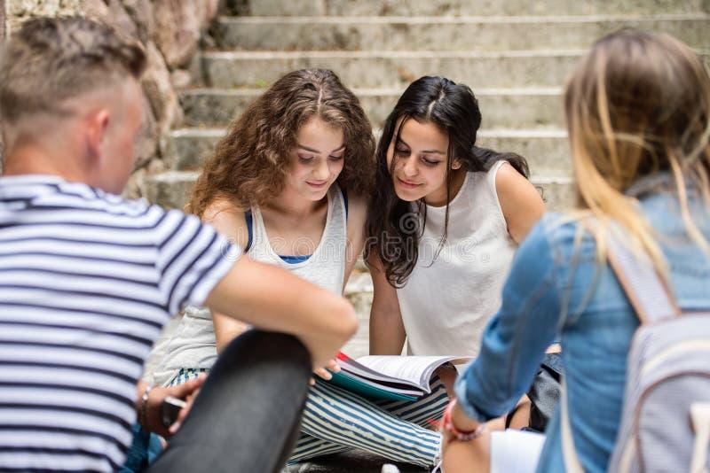 Tonårs- studenter som sitter på stenen, kliver framme av universitet arkivfoto