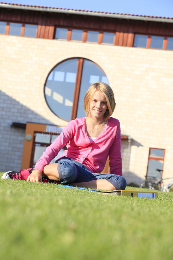 Tonårs- studentsammanträde på gräset utanför skolan royaltyfri fotografi