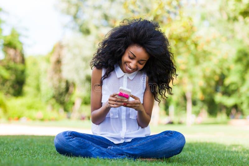 Tonårs- Svart Flicka Som Använder En Telefon Som Ligger På Gräset - Afrikan P Arkivbild