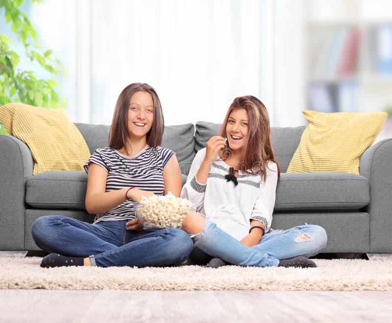 Tonårs- systrar som äter popcorn och håller ögonen på TV royaltyfria bilder