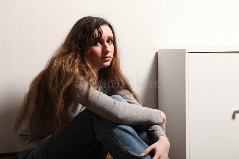 tonårs- tryckt ned home sitting för golvflicka royaltyfria bilder