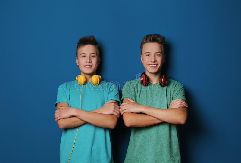 Tonårs- tvilling- bröder med hörlurar arkivbilder