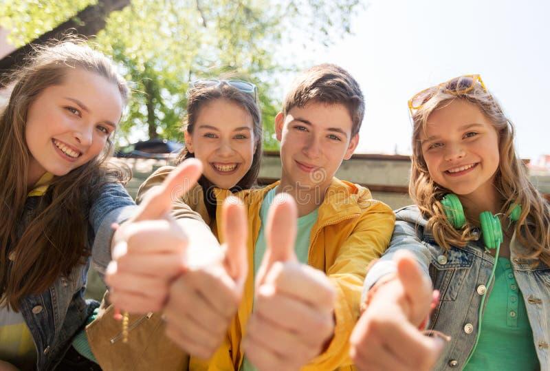 Tonårs- vänner eller studenter som visar upp tummar arkivfoto