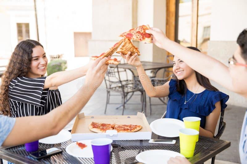 Tonårs- vänner som delar pizza i ett utomhus- kafé royaltyfri bild