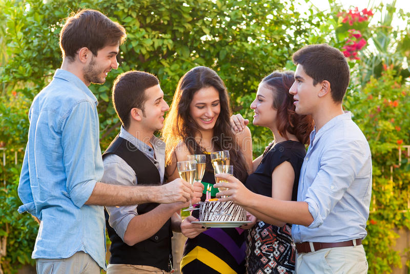 Tonårs- vänner som firar på ett födelsedagparti arkivbild