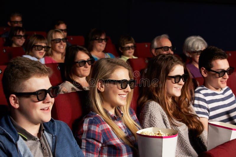 Tonårs- vänner som håller ögonen på filmen 3D i bio arkivfoton