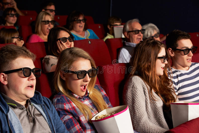 Tonårs- vänner som håller ögonen på filmen 3D i bio arkivbild