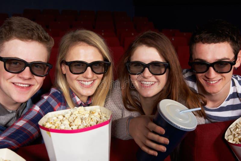 Tonårs- vänner som håller ögonen på filmen 3D i bio arkivfoto