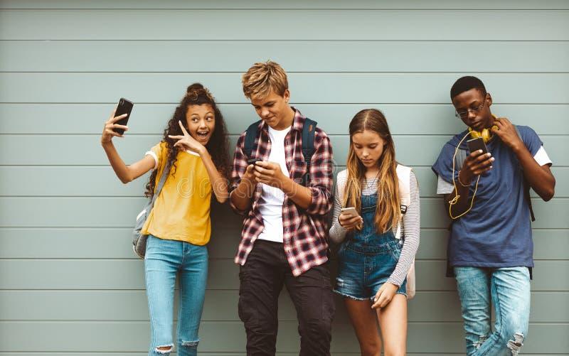Tonårs- vänner som ser deras mobiltelefoner royaltyfri bild