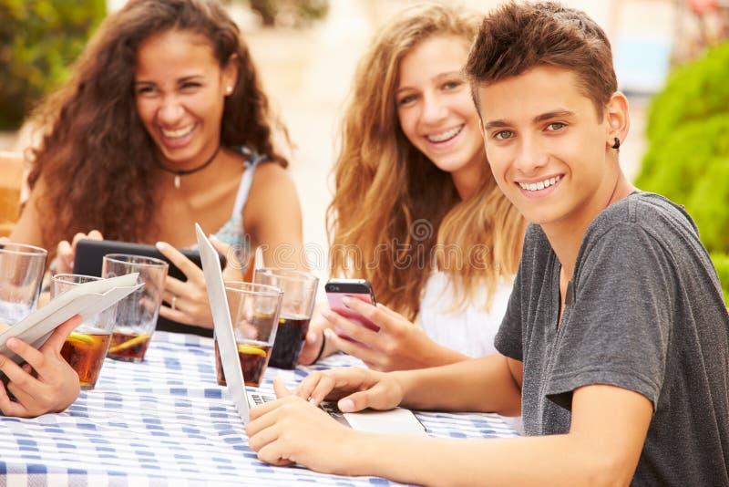 Tonårs- vänner som sitter på Cafï ¿ ½ genom att använda Digital apparater royaltyfri fotografi