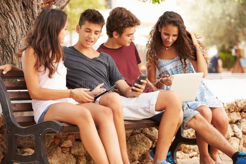 Tonårs- vänner som in sitter, parkerar genom att använda Digital apparater fotografering för bildbyråer