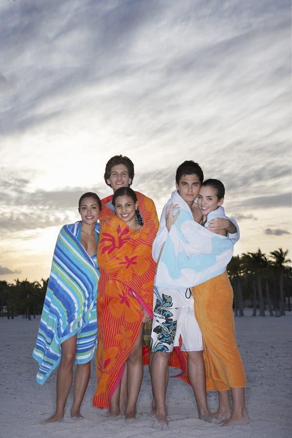 Tonårs- vänner som slås in i handdukar på stranden royaltyfria bilder