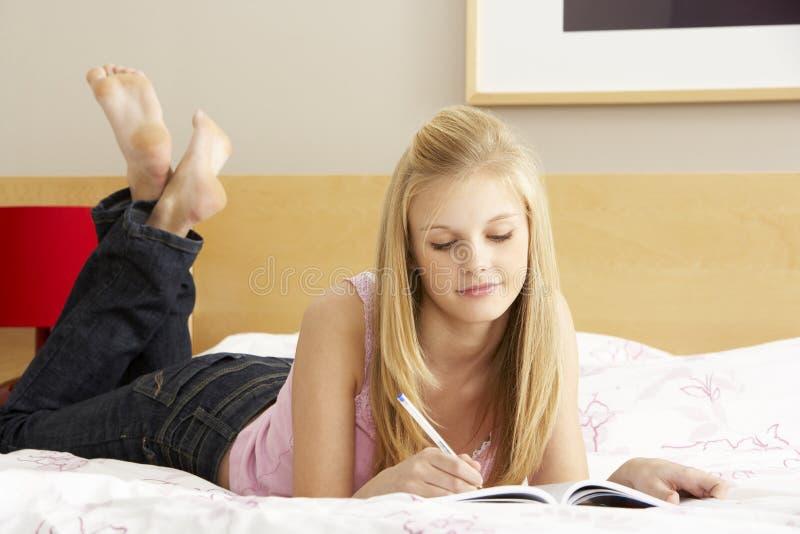 tonårs- writing för sovrumdagbokflicka royaltyfria foton