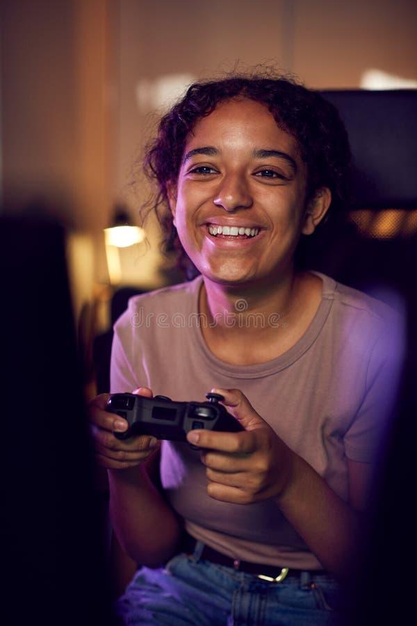 Tonårsflicka med spelplatta som sitter i stol och spelar hemma royaltyfria foton