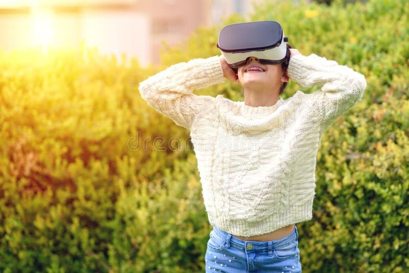 Ton?rig flicka med virtuell verkligheth?rlurar med mikrofon arkivfoton