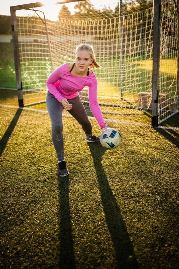 Ton?rig kvinnlig goalie som f?ngar ett skott royaltyfria bilder