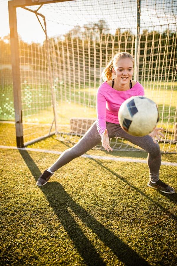 Ton?rig kvinnlig goalie som f?ngar ett skott royaltyfri foto