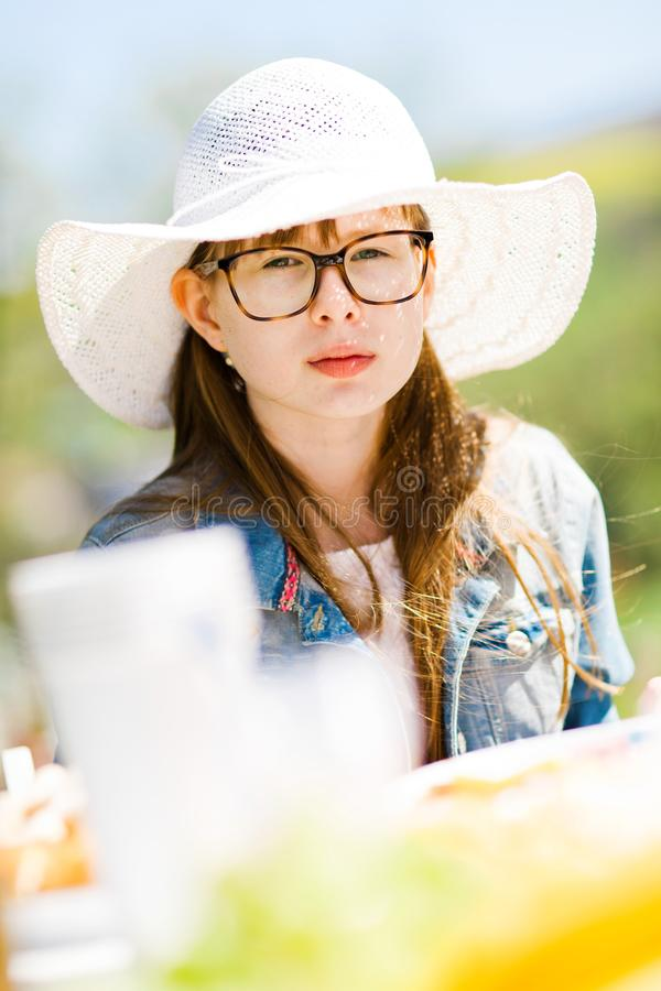 Ton?rig ?ldrig flicka i vit sunhat som sitter vid tabellen p? f?delsedagen gard royaltyfria foton