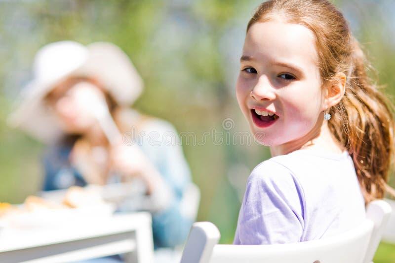 Ton?rig ?ldrig flicka som sitter vid tabellen p? f?delsedagtr?dg?rdpartiet royaltyfri bild