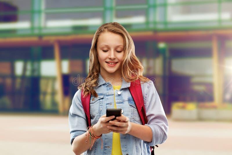 Ton?rig studentflicka med skolap?sen och smartphonen royaltyfria bilder
