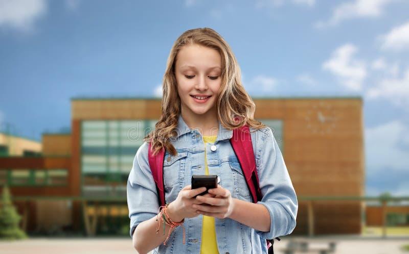 Ton?rig studentflicka med skolap?sen och smartphonen arkivfoton