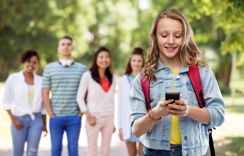 Ton?rig studentflicka med skolap?sen och smartphonen arkivfoto