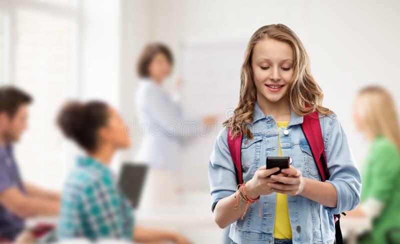 Ton?rig studentflicka med skolap?sen och smartphonen royaltyfri fotografi