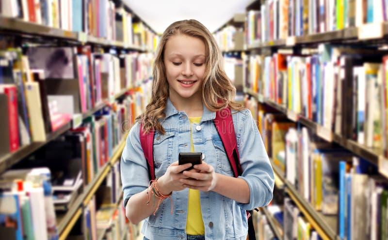 Ton?rig studentflicka med skolap?sen och smartphonen arkivbilder