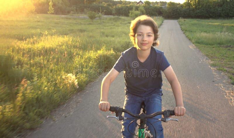 Ton?ring som rider en cykel p? den solbelysta v?gsommaren arkivbilder