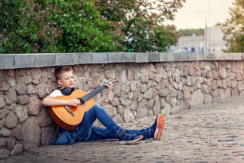 Ton?ringen med den akustiska gitarren och h?rlurar som sitter i, parkerar royaltyfri foto