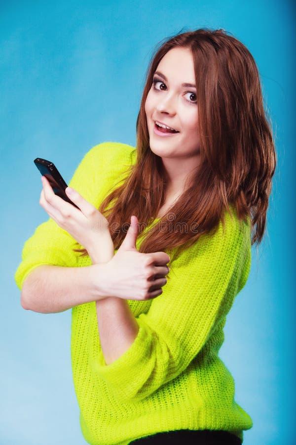 Ton?rs- flicka med att smsa f?r mobiltelefon arkivfoton