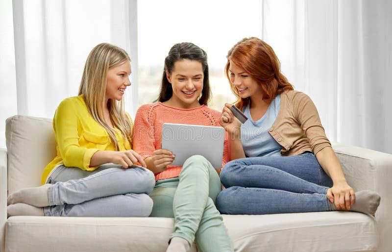 Ton?rs- flickor med den minnestavlaPC och kreditkorten royaltyfri fotografi