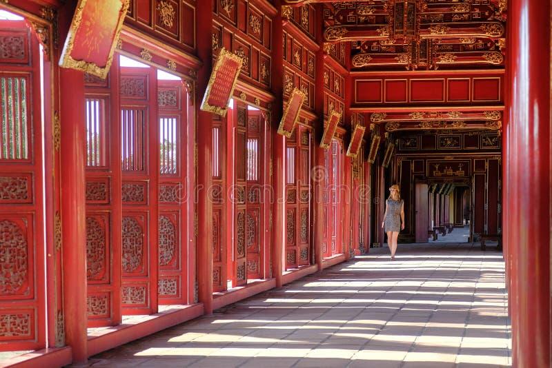 Ton/Vietnam, 17/11/2017: Kvinna som passerar till och med en röd dekorativ pavillion i citadellkomplexet i ton, Vietnam fotografering för bildbyråer