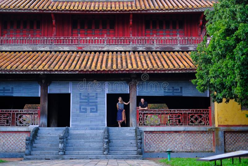 Ton/Vietnam, 17/11/2017: Par som står inom ett traditionellt hus med det dekorativa belade med tegel taket i citadellen av tonen, arkivbilder
