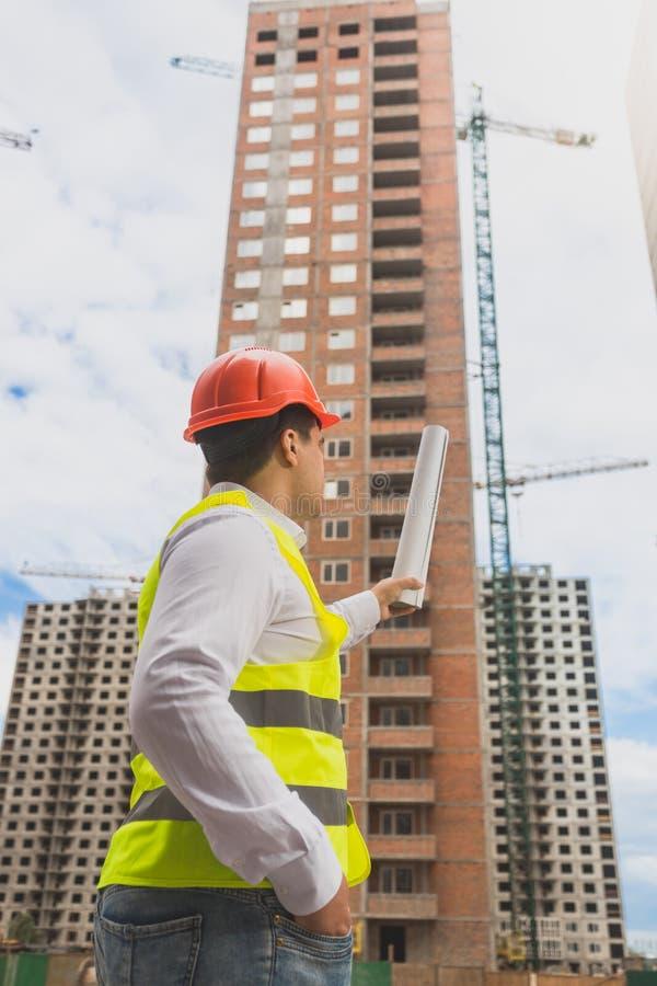 Tonad bild av arkitekten som pekar på byggnad under konstruktion royaltyfri foto