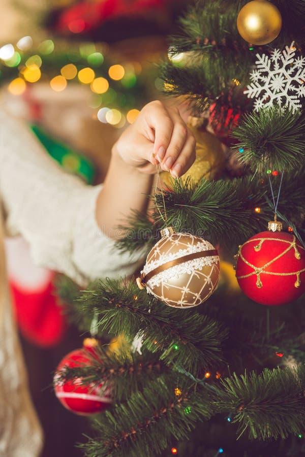 Tonad bild av den unga kvinnan som sätter den guld- struntsaken på jul tr royaltyfria foton