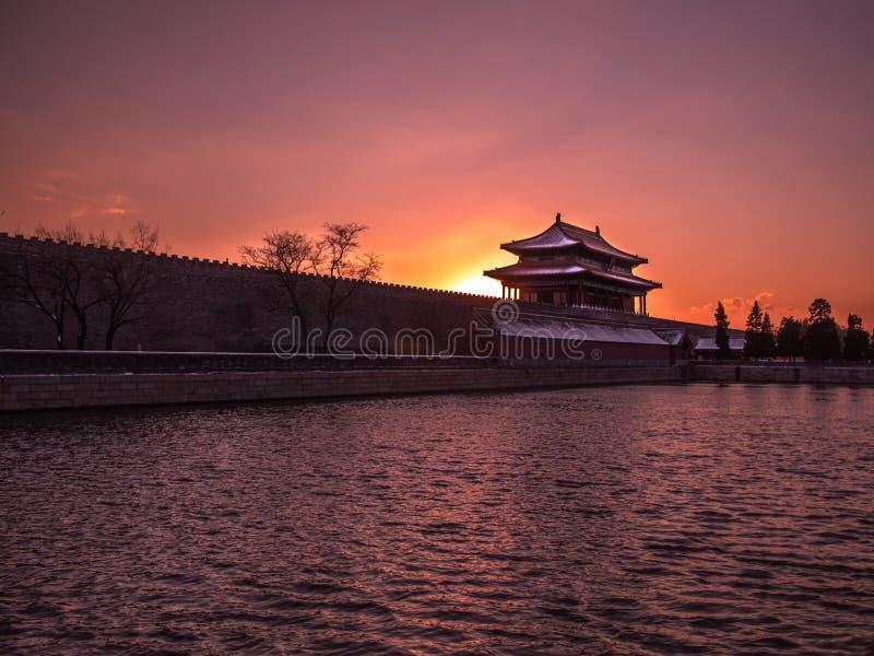 Tonad bild av fästningen med ett torn Forbidden City i Peking på bakgrunden av solnedgången på klar himmel royaltyfri bild